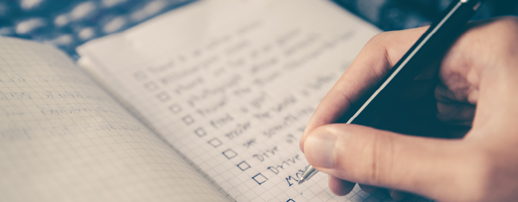 Close up photo of a person checking off items on a checklist